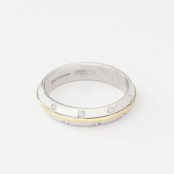 a diamond set 7 stone ring with a white gold band and a yellow gold centre