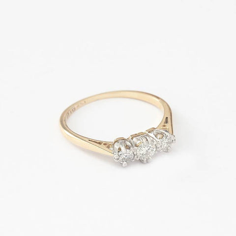a vintage yellow gold diamond set 3 stone ring with a white claw setting and yellow gold band