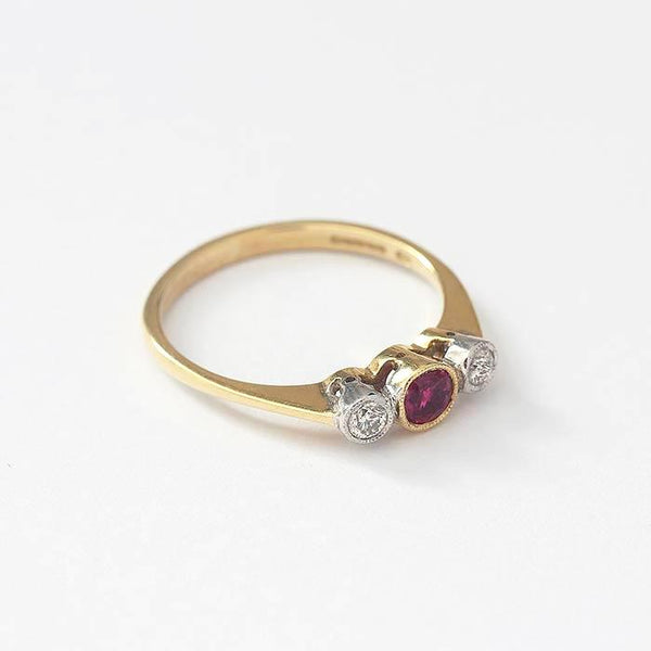 a 3 stone central ruby and diamond round shaped grain set ring in yellow gold