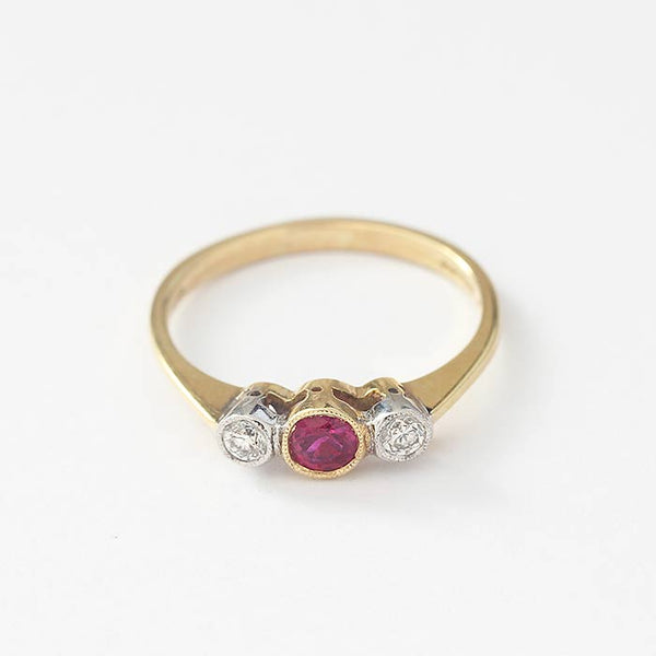 a vintage style ruby and diamond 3 stone ring in yellow gold and grain settings