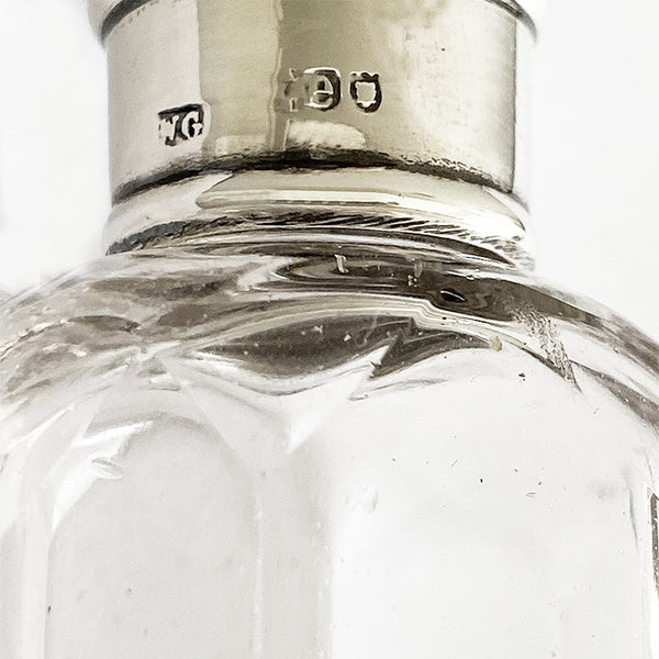 an antique silver and glass small perfume bottle dated 1900 with engraved v on the top