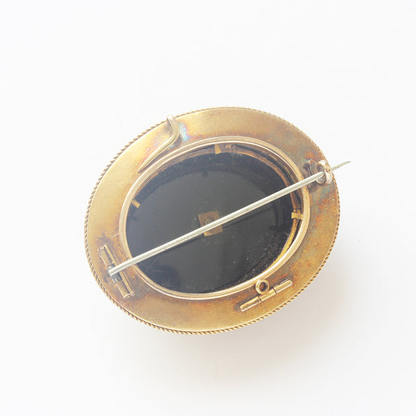 an antique mourning brooch oval with roped edge and onyx enamel and diamond