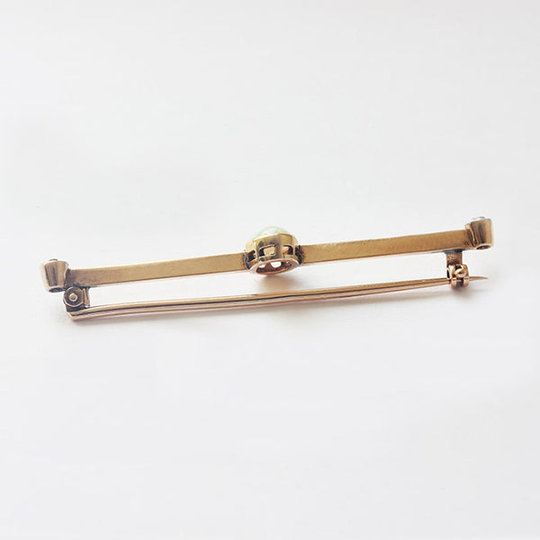 a secondhand yellow gold bar brooch with a central oval opal and 1 old cut diamond each end