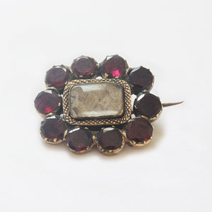 a garnet set floral shaped mourning gold brooch with hair in the centre