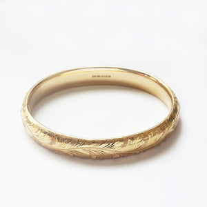 a superb 18 carat yellow gold oval solid bangle with floral scroll pattern and full hallmark at marston barrett in lewes sussex