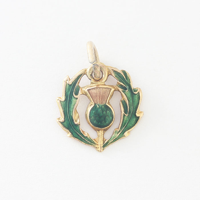 a vintage yellow gold thistle with green enamel for a charm bracelet