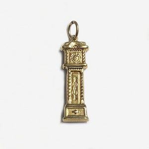 a gold grandfather clock charm in yellow gol