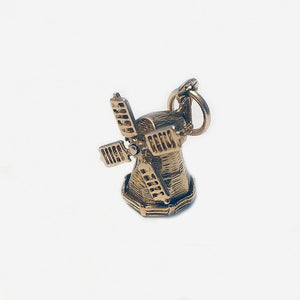 a vintage gold spinning windmill charm with patterns