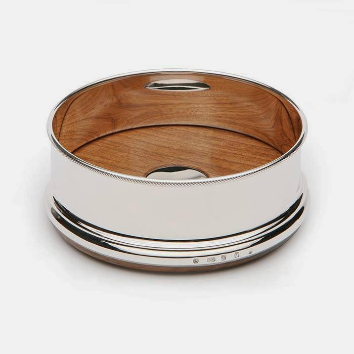 a silver heavy wine coaster with a full hallmark and a roped edge