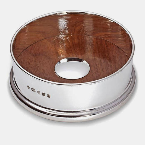 a britannia silver wine coaster which is polished and has a full hallmark on the side with american walnut base