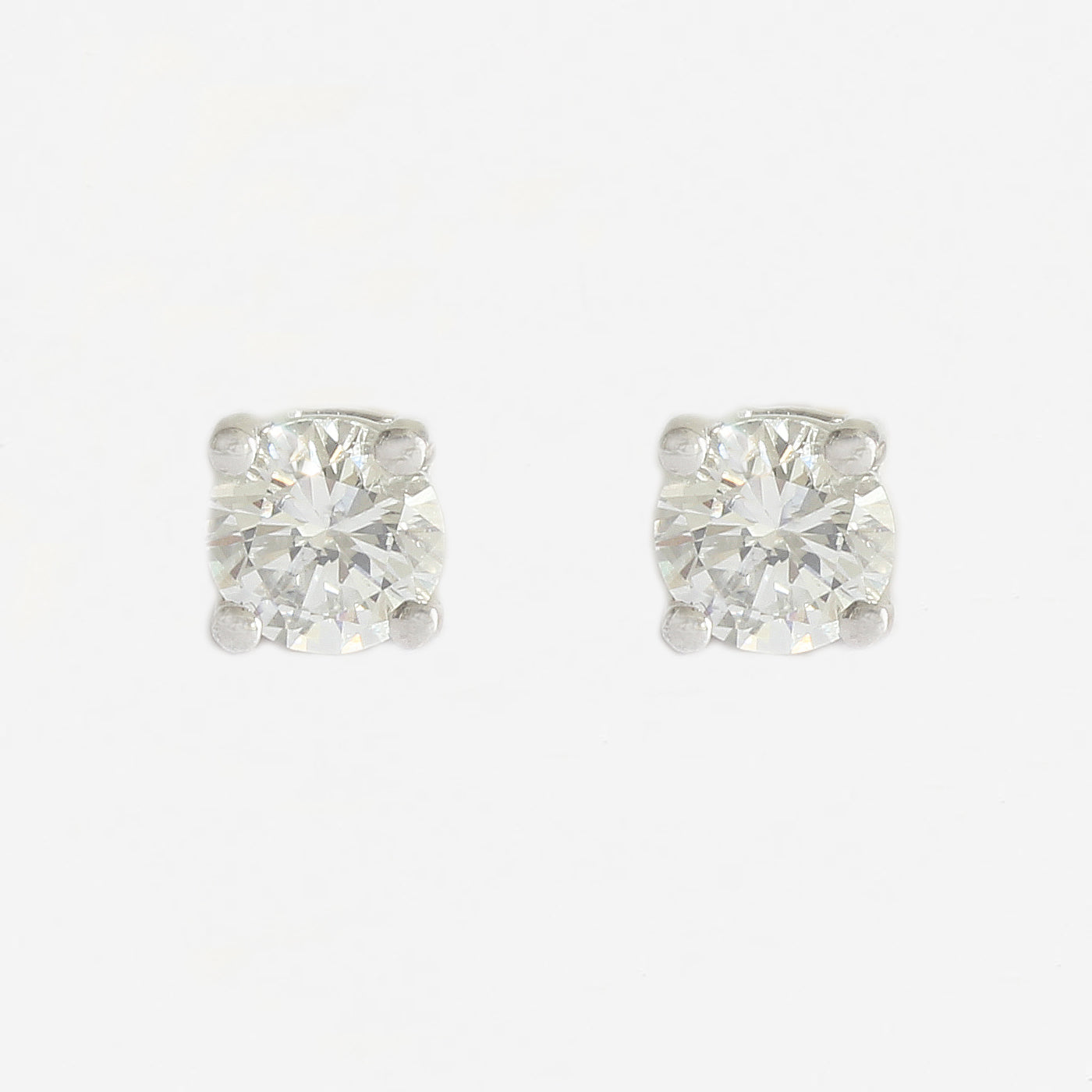 a four claw set of round diamond stud earrings in white and yellow gold