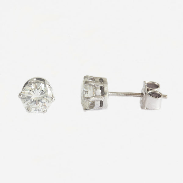 a vintage pair of six claw white gold round diamond solitaire stud earrings