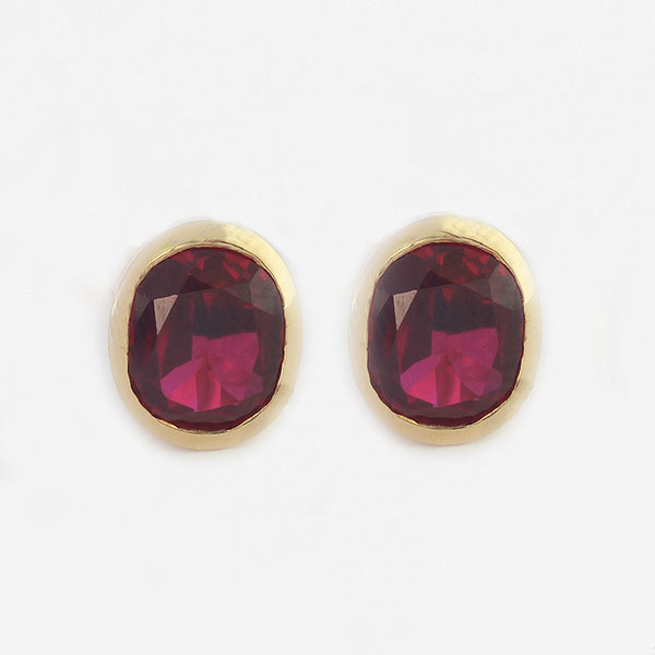 a pair of yellow gold 18 carat oval ruby stud earrings in a rub over setting
