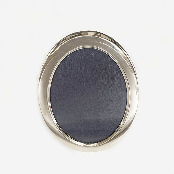 a modern silver oval small photo frame dated 2007