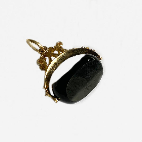 a vintage yellow gold fob swivel design with a 3 sided onyx stone