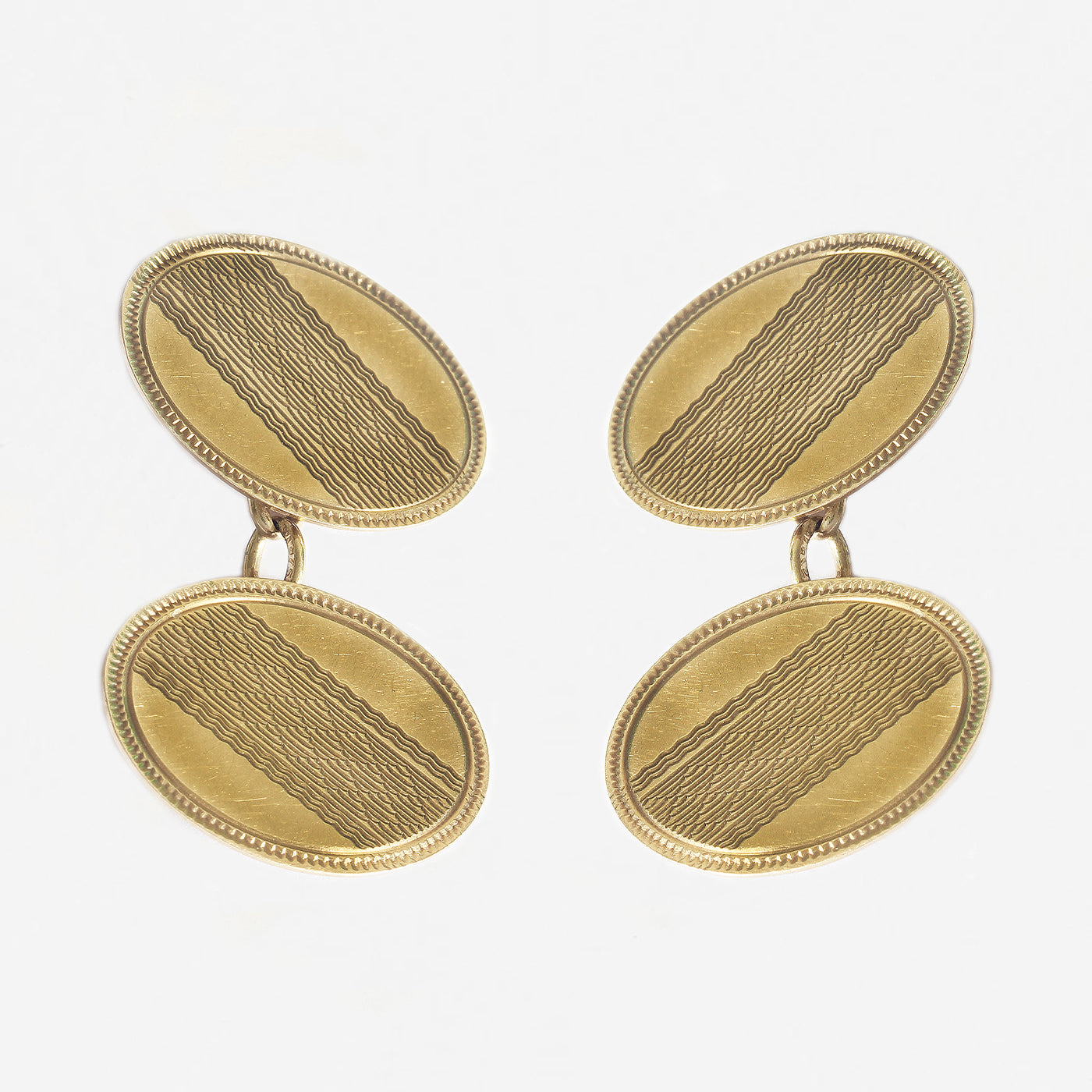 a secondhand pair of yellow gold engine turned engraved oval cufflinks with chain connectors