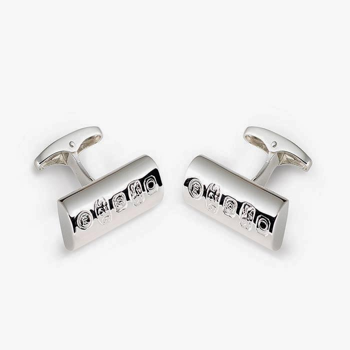 a set of modern silver cufflinks with a half pipe shape and post fitting with the hallmark on the front