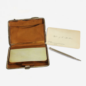 an antique finger purse in silver with pencil and card dated 1904