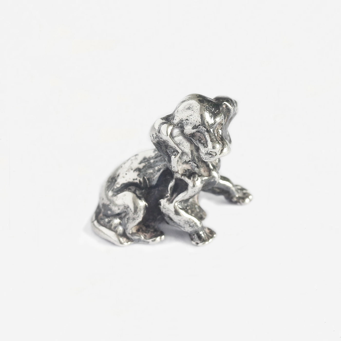 a small silver puppy dog figure dated 1987