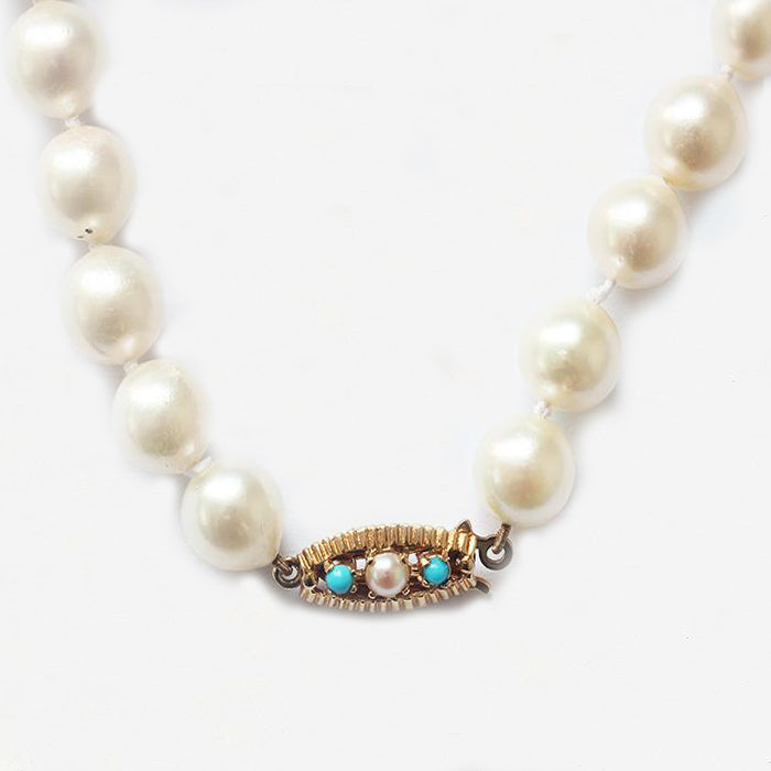 a string of pearls with a turquoise and pearl gold clasp