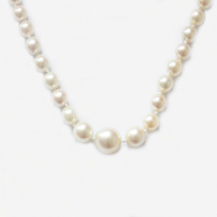 a string of graduated pearls with a rectangular gold clasp
