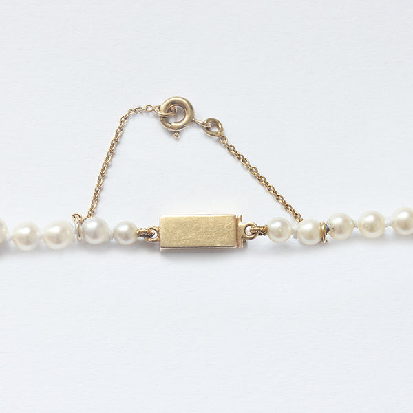 a string of graduated pearls with a gold rectangular satin polished clasp and safety chain
