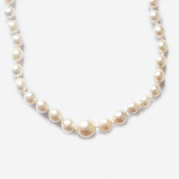 a silver string of pearls with an oval silver clasp