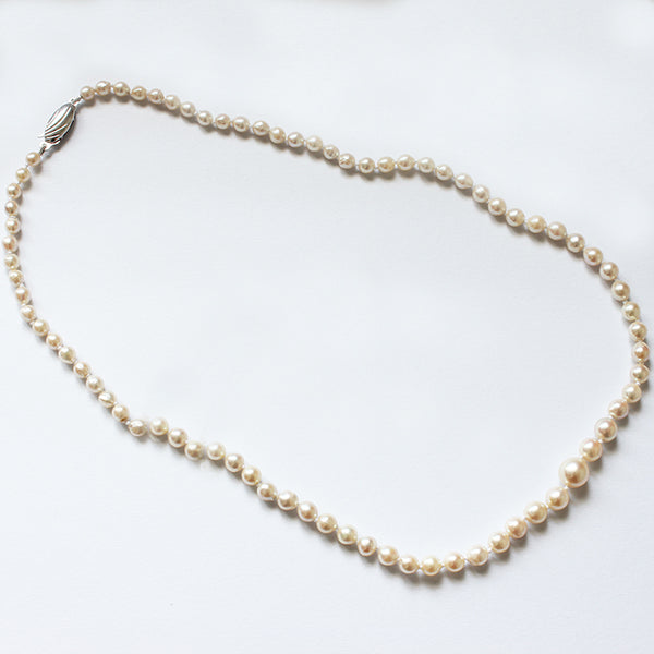 a preowned string of pearls with a graduated pattern and a silver oval clasp