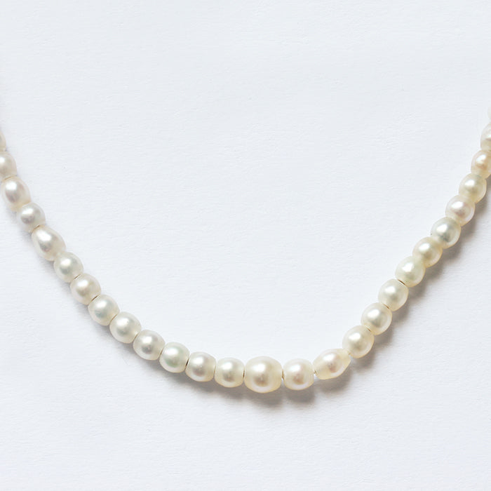 a string of pearls with a platinum torpedo shaped clasp and safety chain