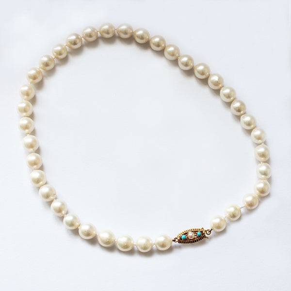 a secondhand row of single pearls with a turquoise and pearl clasp in gold