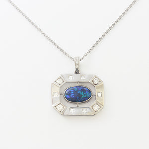 a superb black opal with blues and greens with diamonds in an octagonal border and fine curb chain