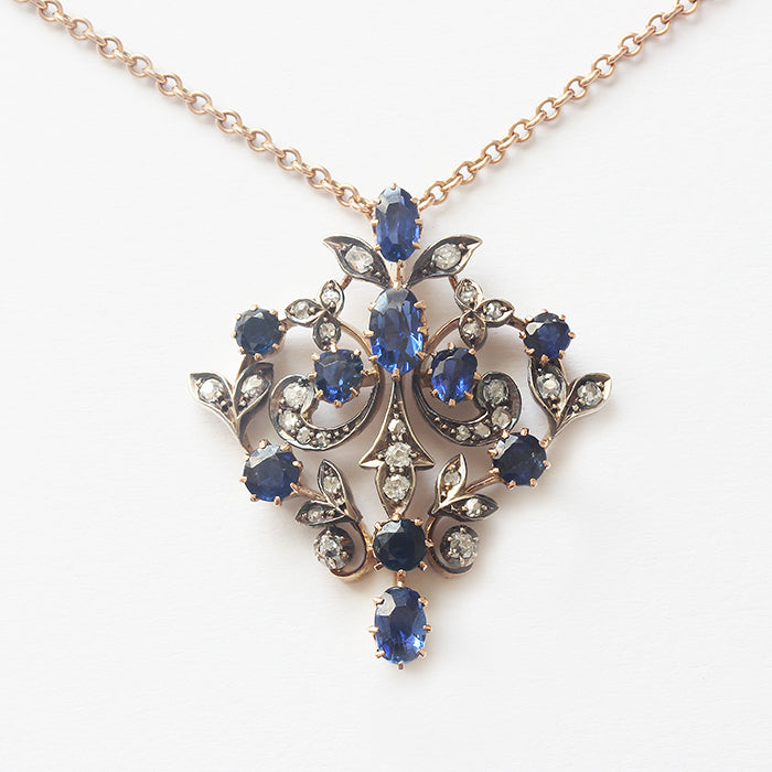 a stunning sapphire and diamond cluster floral brooch or pendant on an antique chain in gold  from the edwardian era