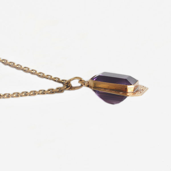 a patterned yellow gold pendant with large amethyst set and a yellow gold chain