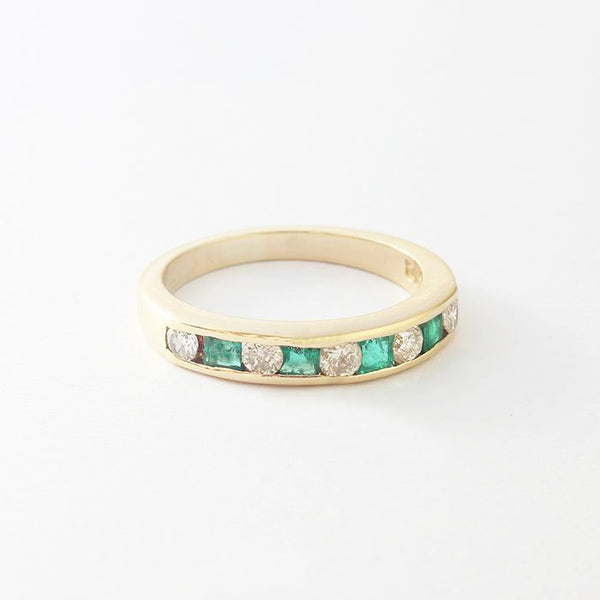 an emerald diamond half eternity ring channel set in yellow gold  Edit alt text