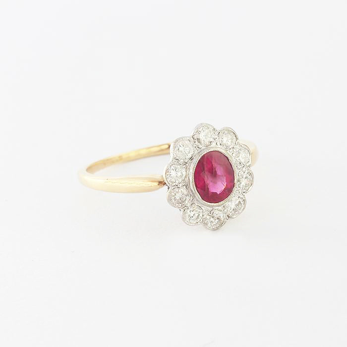 a beautiful ruby and diamond set oval cluster ring in white and yellow gold  Edit alt text
