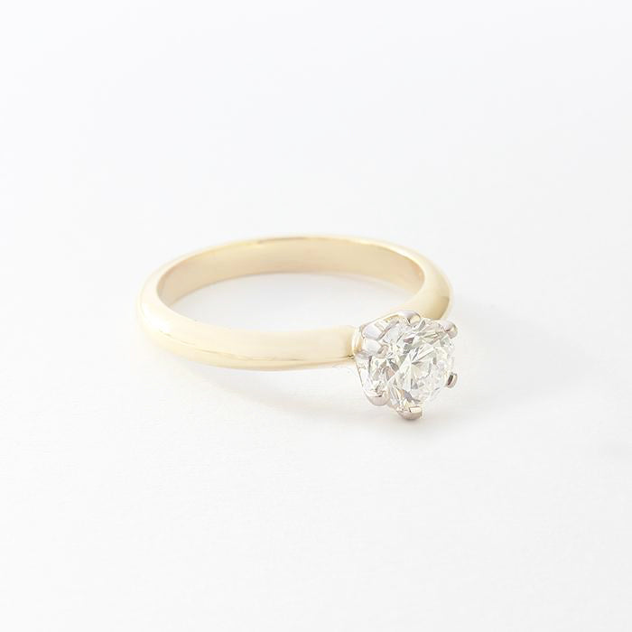 a beautiful diamond engagement ring with 6 claw setting and yellow gold band and certificate