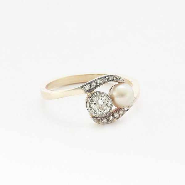 a diamond and pearl cross over design ring in yellow gold  Edit alt text