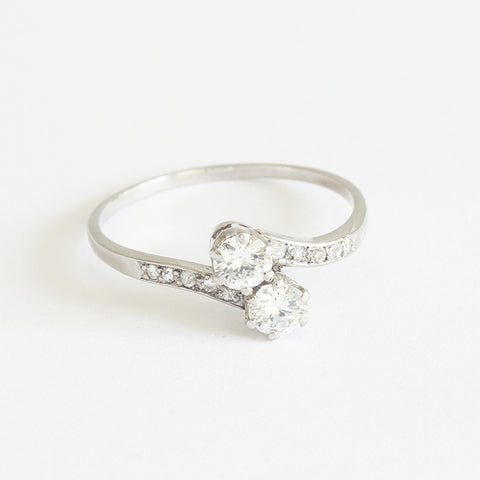 a secondhand diamond set cross over ring with diamond shoulders in white gold