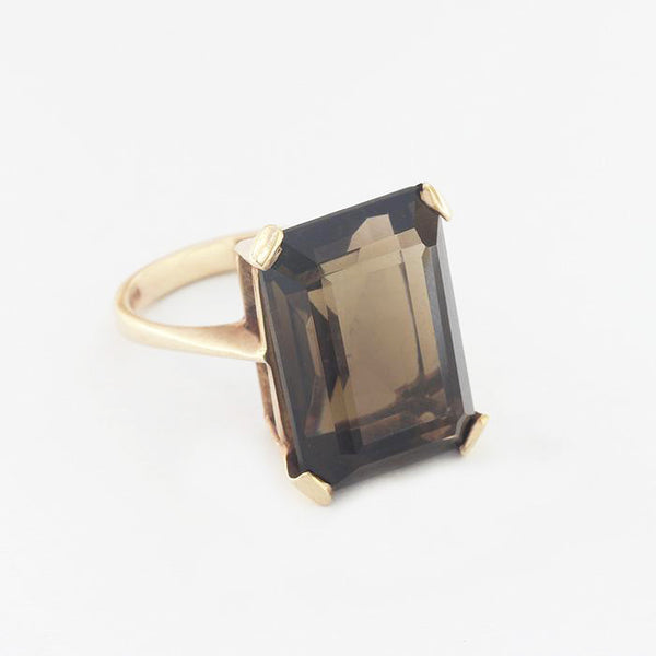 a large rectangular smokey quartz single stone claw set ring in yellow gold
