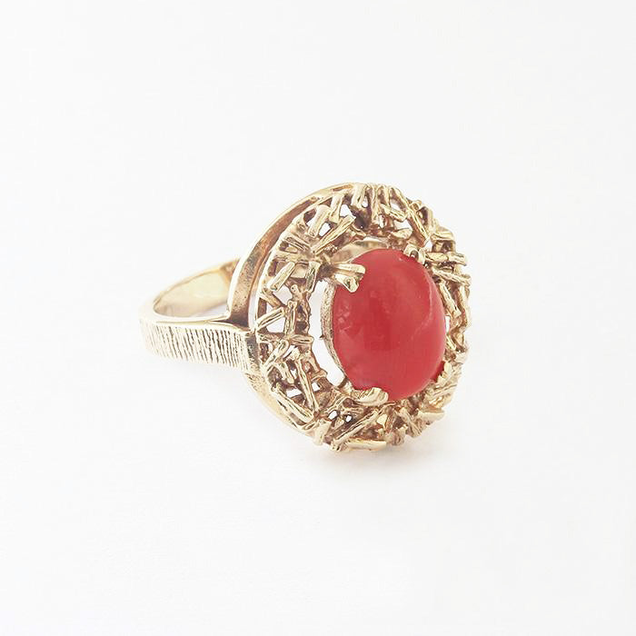 a beautiful coral set nest design ring in yellow gold with a bark finish band