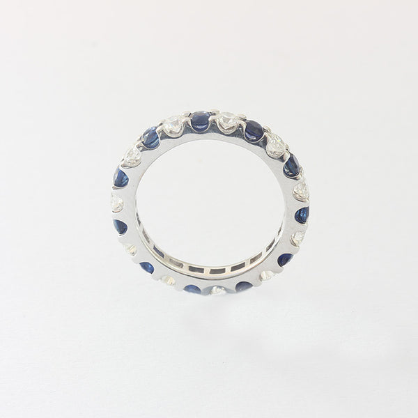 a white gold sapphire and diamond set full eternity ring with a claw setting