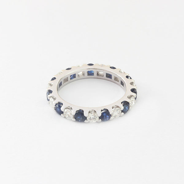 a round sapphire and diamond claw set full eternity ring in white gold