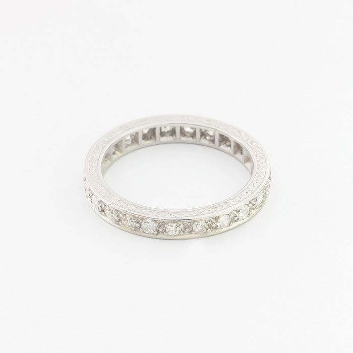 a decorative secondhand diamond eternity ring with scroll engraving around the edges
