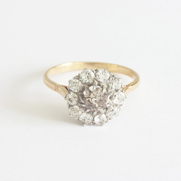 a beautiful diamond cluster ring in gold and silver with a centre cinnamon diamond