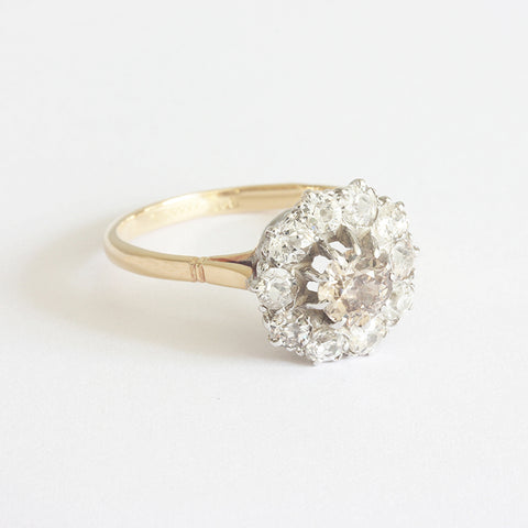 a diamond cluster ring with a central cinnamon diamond and white diamond surround in gold and silver