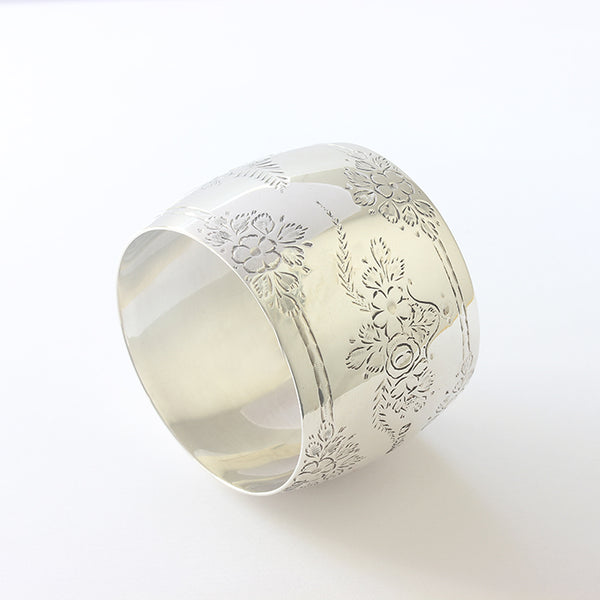 a secondhand old silver napkin ring with floral pattern