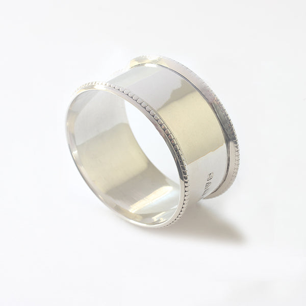 a secondhand silver serviette ring with a beaded edge and dated 1921