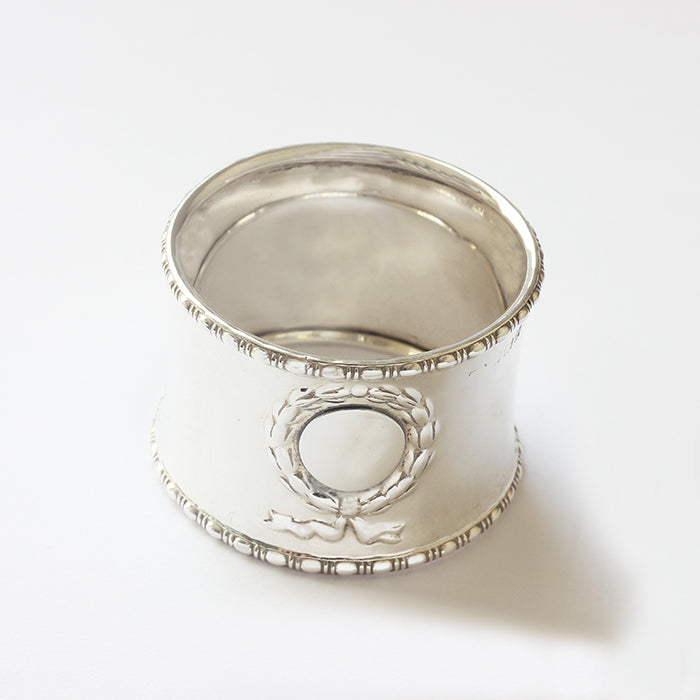 a silver napkin ring with patterned edges and a  ribbon motif for engraving