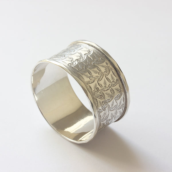 a victorian napkin ring in silver dated 1891 with leaf pattern and  shield shape for engraving