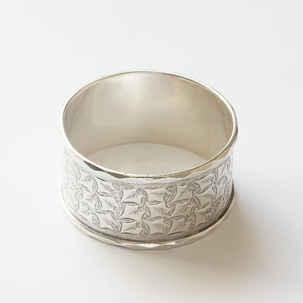 a leaf pattern silver serviette ring dated 1891 with a leaf pattern and shield motif for engraving